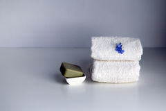 Stack of white loop towels and soap bar. Royalty Free Stock Images