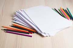 Stack of white papers and pencils with paper clips on office table. Stack of paperwork. Education or business concept. Stack of white papers and pencils with royalty free stock photos