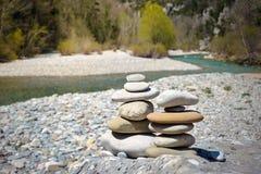 Stack of white pebbles stone against blue mountain stream background stock photos