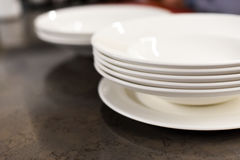 A stack of white plates on a dark kitchen table Stock Photography