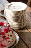 Stack of white plates and a wedding cake on a wooden table Royalty Free Stock Photography