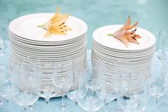 Stack of white plates and wine glasses Stock Photos