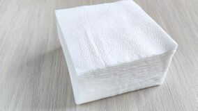 Stack of white square napkins on wooden table. Female hand takes few paper napkins from side. Close-up, daylight