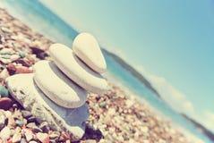 Stack of white stones balancing on the pebbly beach; retro Stock Image