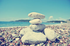 Stack of white stones balancing on the pebbly beach; retro Royalty Free Stock Photography