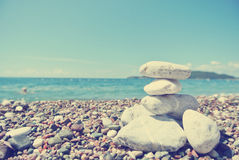 Stack of white stones balancing on the pebbly beach; retro Royalty Free Stock Photos