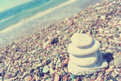 Stack of white stones balancing on the pebbly beach; retro Royalty Free Stock Image