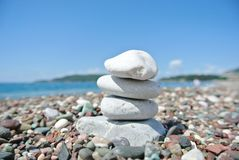 Stack of white stones balancing on the pebbly beach Stock Images