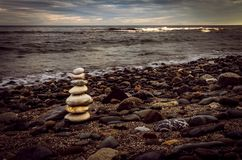 Stack of white stones on the rocky beach. royalty free stock image