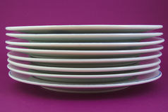 Stack of white and used dishes on purple Stock Image