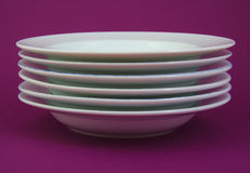 Stack of white and used dishes on purple Stock Photos