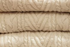 Stack of white woolen knitted sweaters close-up, texture, background stock image