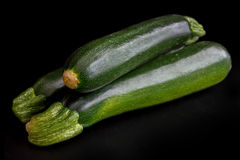 Stack of whole courgettes isolated on black. Royalty Free Stock Photography