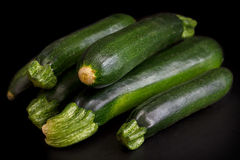 Stack of whole courgettes isolated on black. Stock Photo