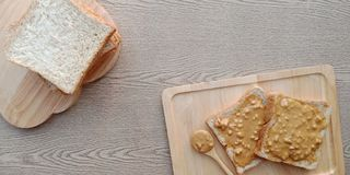 Stack of whole wheat bread and some peanut butter on top. stock photo