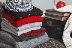 Stack of winter clothes and books with glossy edge Stock Image