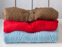 Stack of women's sweaters and cardigans. Stock Photos