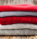 Stack of women's sweaters in grey and red colors Royalty Free Stock Image