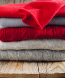 Stack of women's sweaters in grey and red colors Stock Photo