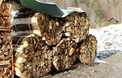 Stack of wood in winter time in an alpine setting. Royalty Free Stock Photo