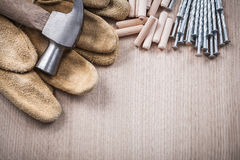 Stack of wooden dowels claw hammer leather working gloves and st Stock Photos