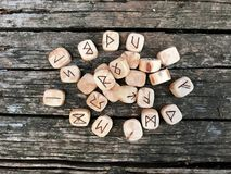 A stack of wooden runes at forest. Wooden runes lie on a old wood background. Runes are cut from wooden blocks. On each royalty free stock photos