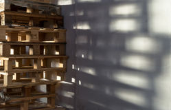 Stack of Wooden Storage Pallets. Single stack of many wooden storage packing pallets casting a shadow on a white factory wall Royalty Free Stock Images