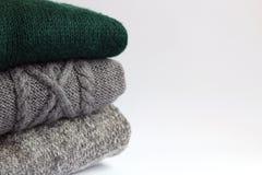Stack woolen tröjor på en ljus bakgrund fotografering för bildbyråer
