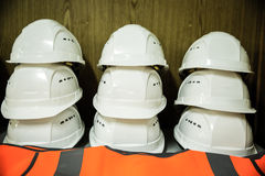 Stack of workers' helmets. Stack of white construction workers' helmets with reflective protection clothes underneath Stock Photo