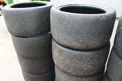 Stack of worn racing tyres. At car garage stock image