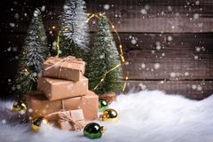 Stack of wrapped presents, decorative fir trees, golden and green balls and fairy lights on white fur background against vintage stock photo