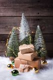Stack of wrapped presents, decorative fir trees, golden and green balls and fairy lights stock image