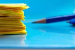 A stack of yellow paper and a pencil on a blue table close-up. stock photography