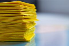 Stack of yellow paper on blue table stock photo