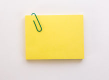 Stack of yellow sheets of paper with green paper clip on a white Stock Photography