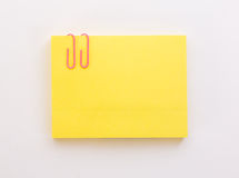 Stack of yellow sheets of paper with pink paper clip on a white Royalty Free Stock Photo