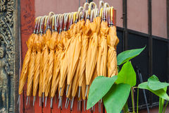 Stack of yellow umbrellas for sale at a stall Stock Image