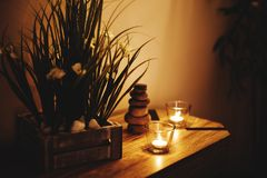 Stack of zen stones and aromatic candles on table. Zen concept. royalty free stock photography