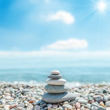 Stack of zen stones near sea and clouds with sun Royalty Free Stock Photo