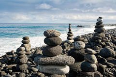 Stack of zen stones over water and blue sky. Royalty Free Stock Image
