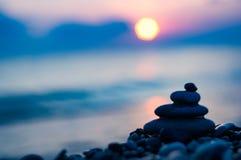Stack of zen stones on pebble beach. Folded pyramid Zen pebble stones on the sea beach at sunset stock image