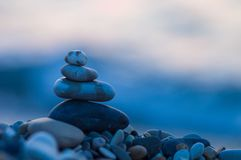 Stack of zen stones on pebble beach. Folded pyramid Zen pebble stones on the sea beach at sunset stock photo