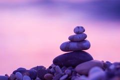 Stack of zen stones on pebble beach. Folded pyramid Zen pebble stones on the sea beach at sunset royalty free stock image