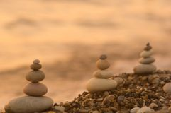 Stack of zen stones on pebble beach. Folded pyramid Zen pebble stones on the sea beach at sunset royalty free stock photography