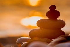 Stack of zen stones on pebble beach. Folded pyramid Zen pebble stones on the sea beach at sunset stock images