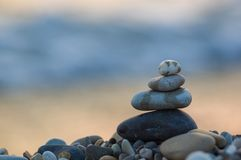 Stack of zen stones on pebble beach. Folded pyramid Zen pebble stones on the sea beach at sunset royalty free stock images