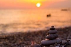Stack of zen stones on pebble beach. Folded pyramid Zen pebble stones on the sea beach at sunset stock photography
