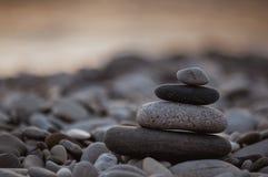 Stack of zen stones on pebble beach. Folded pyramid Zen pebble stones on the sea beach at sunset royalty free stock photos