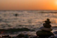 Stack of zen stones on pebble beach. Folded pyramid Zen pebble stones on the sea beach at sunset stock photos