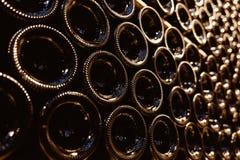 Stacked aging wine bottles in modern cellar Stock Image